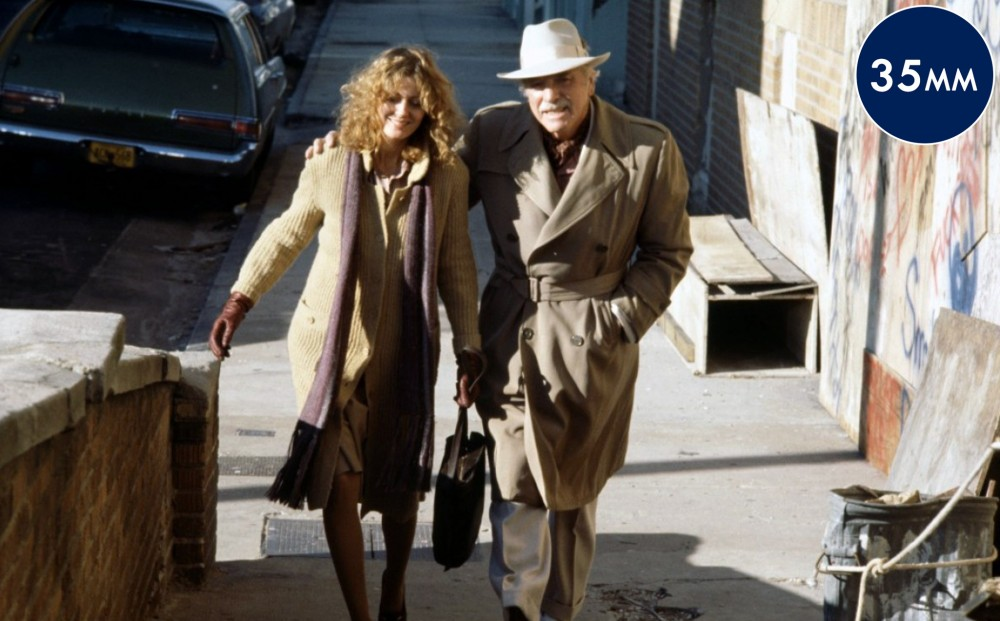 Actors Burt Lancaster and Susan Sarandon walk down the street together, his arm around her shoulder.