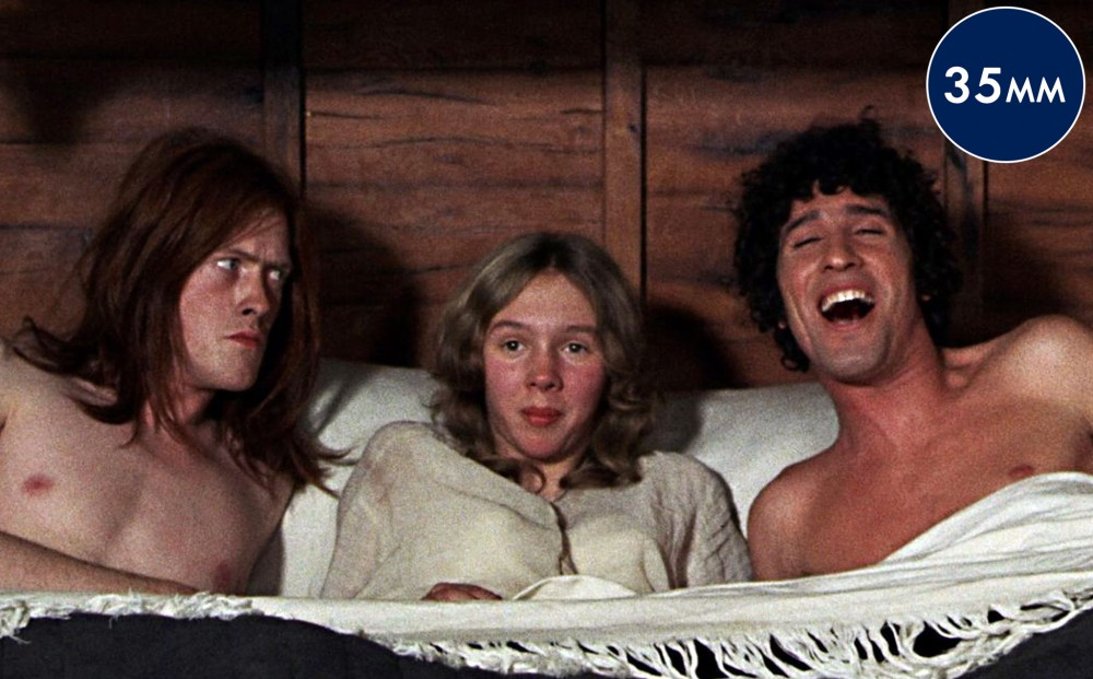 A women wearing a nightgown lays on a bed between two shirtless men—one looks angry at the other, who is laughing.