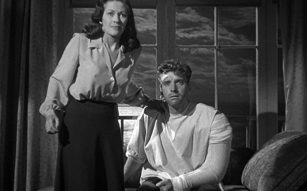 Actor Burt Lancaster has a cast on one arm; Yvonne De Carlo stands beside him with her arm on his shoulder.