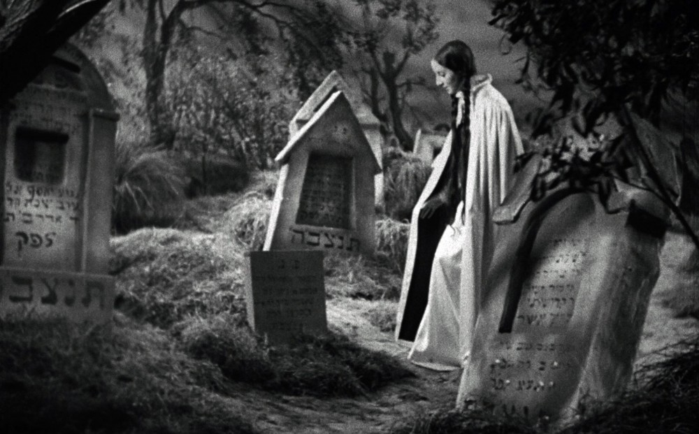 The pale woman with two long, dark braids stands in a cemetery in front of a headstone.