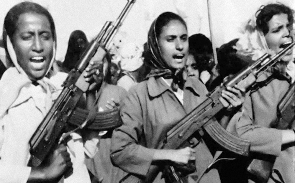 Three women wearing scarves over their heads, holding machine guns.