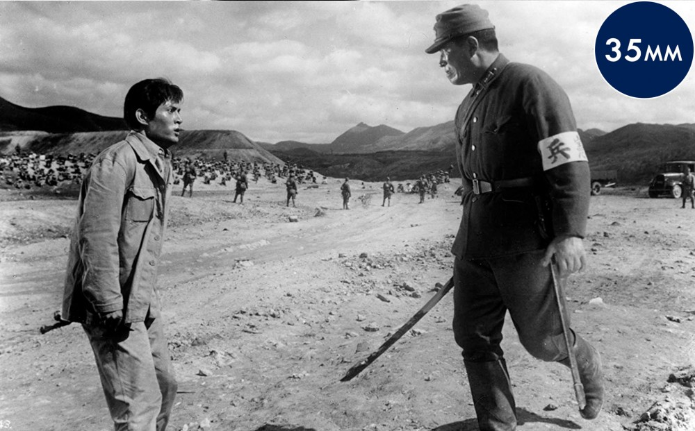A soldier in uniform approaches actor Tatsuya Nakadai antagonistically.