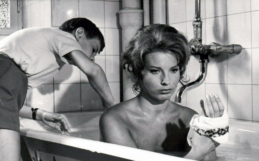 Actor  Gunnel Lindblom takes a bath; Jörgen Lindström stands outside the tub next to her.