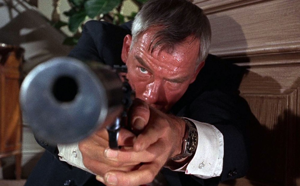 Actor Lee Marvin points a gun, his forehead covered in sweat.