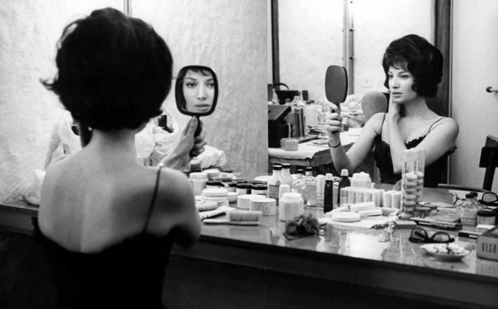 Actor Jeanne Moreau sits at a vanity in front of a large mirror, while also looking in a hand mirror.