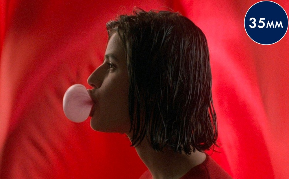 Actor Irene Jacob in profile against a red background, blowing a bubble with chewing gum.