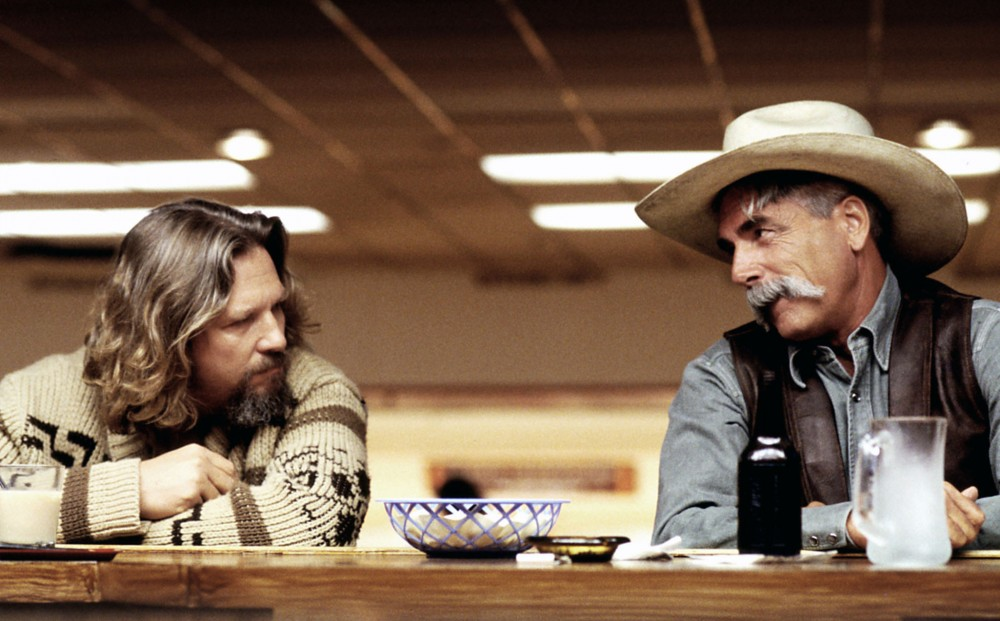 Actor Jeff Bridges sits at a bar with a man wearing a cowboy hat and large mustache.
