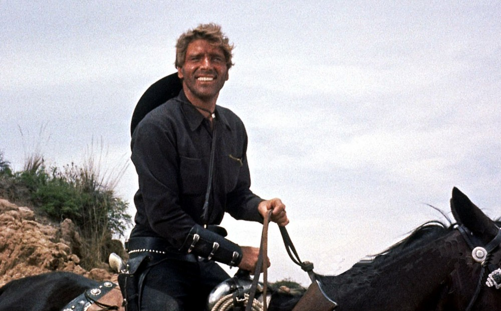 Actor Burt Lancaster rides a horse and greens.