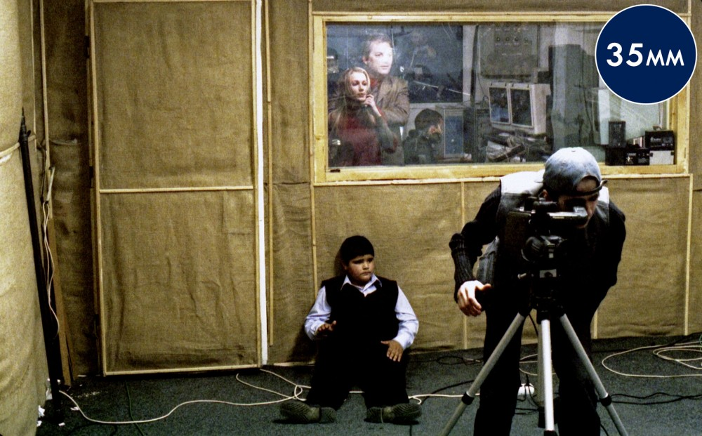 A camera person peers through his lens; a child sits on the floor behind him, and behind the child are more crew people in a separate room with computers.