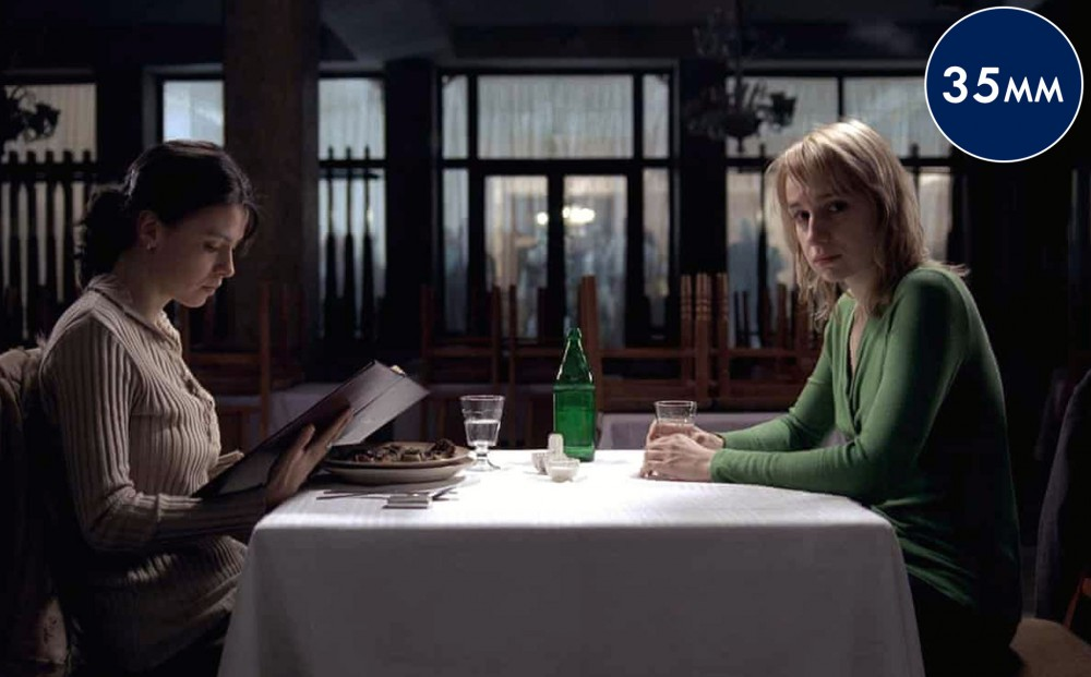 Two women sit together at a table in a restaurant; one looks at the menu and the other looks off, upset.