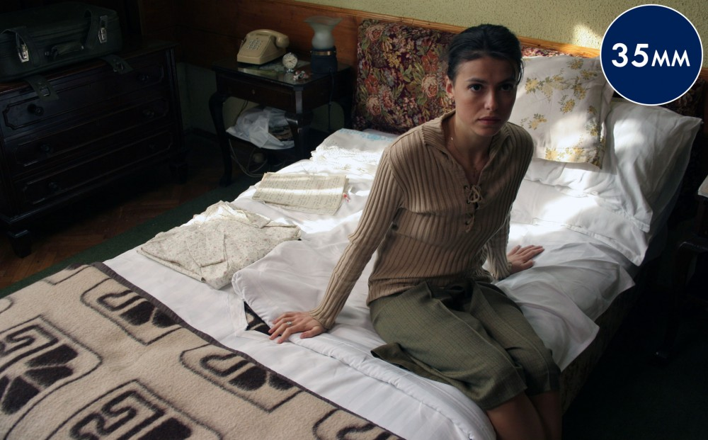 A woman sits on a bed, looking up.