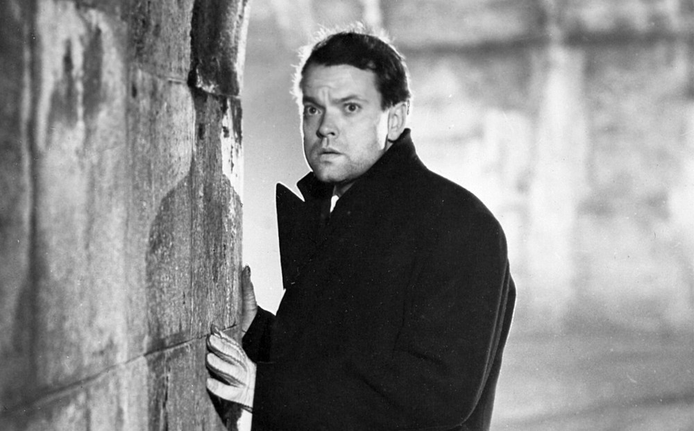 Actor Orson Welles, wearing a coat and gloves, stands at the edge of a tunnel, looking concerned.