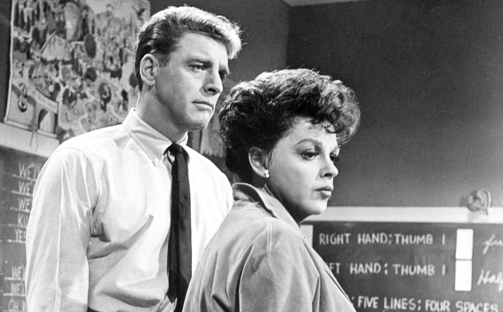 Actor Burt Lancaster stands next to Judy Garland, though they don't speak.