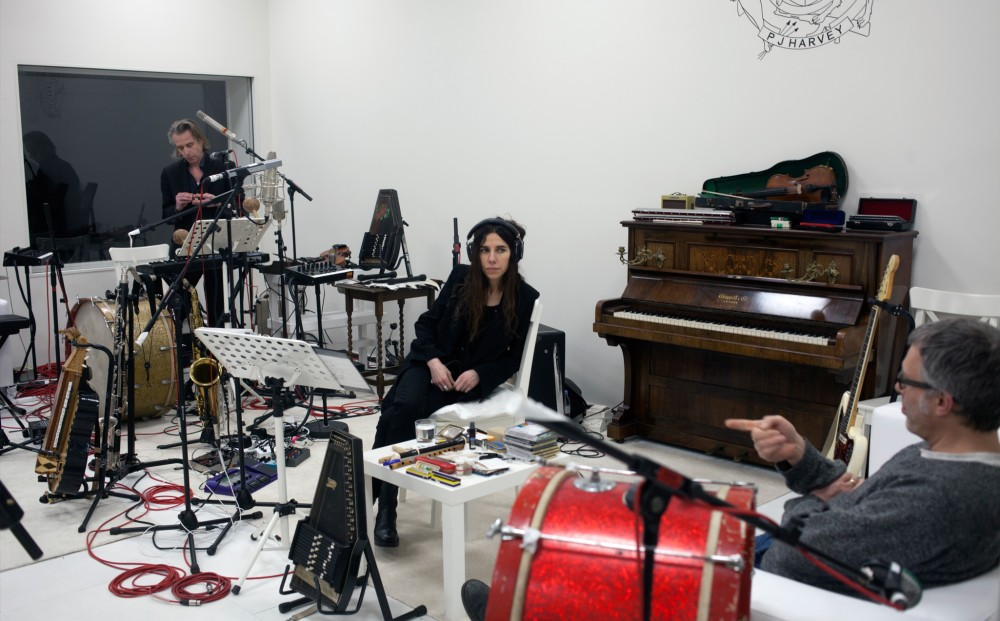 Musician PJ Harvey sits in a white recording studio with two men; there are instruments and microphones all over.