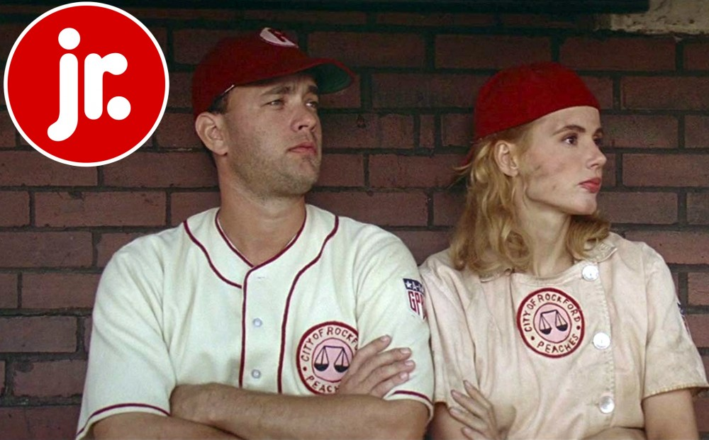 Actors Tom Hanks and Geena Davis stand against a brick wall, both wearing baseball uniforms.
