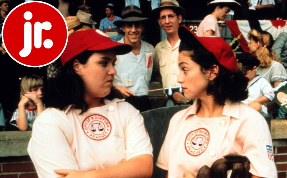 Actors Geena Davis and Rosie O'Donnell talk on the field, wearing baseball uniforms.