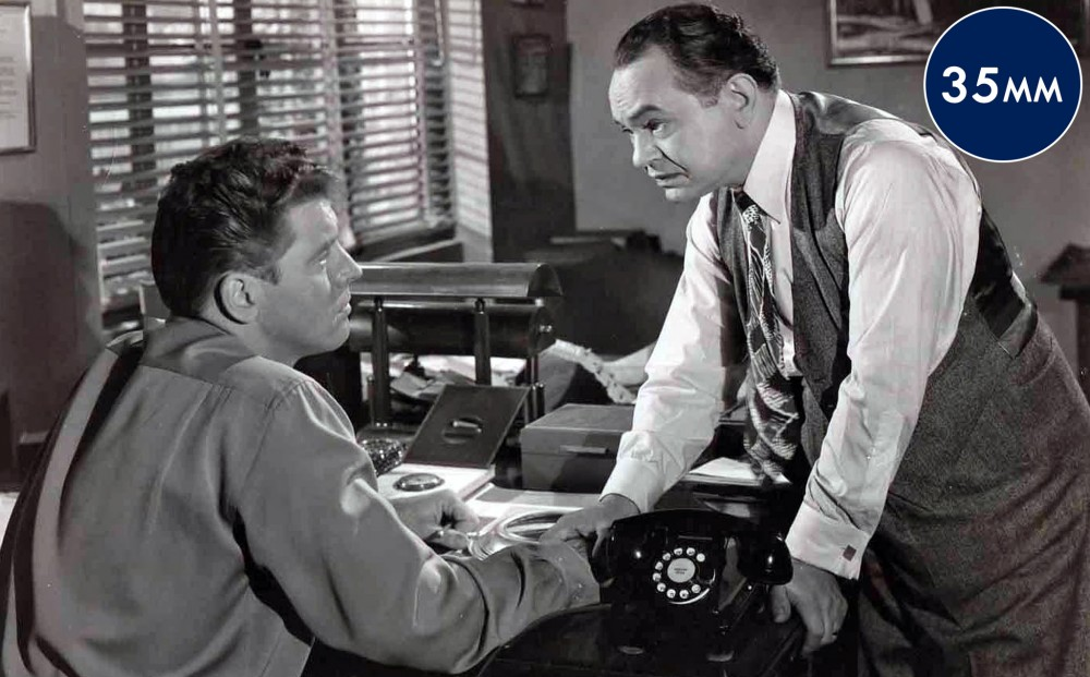 Actor Edward G. Robinson leans on the desk where Burt Lancaster is seated, and holds onto his wrist.