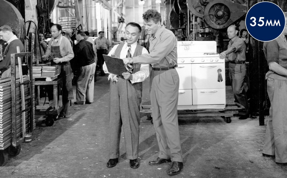 Actors Edward G. Robinson and Burt Lancaster look at something on a clipboard, on the floor of a factory.