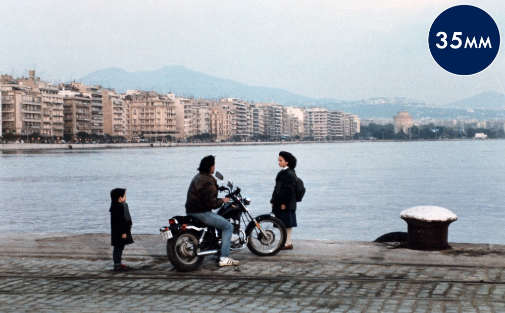 Two children stand by a man sitting on a motorcycle.