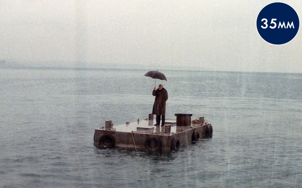 A man holding an umbrella stands on a floating dock, in the middle of a body of water with grey skies.