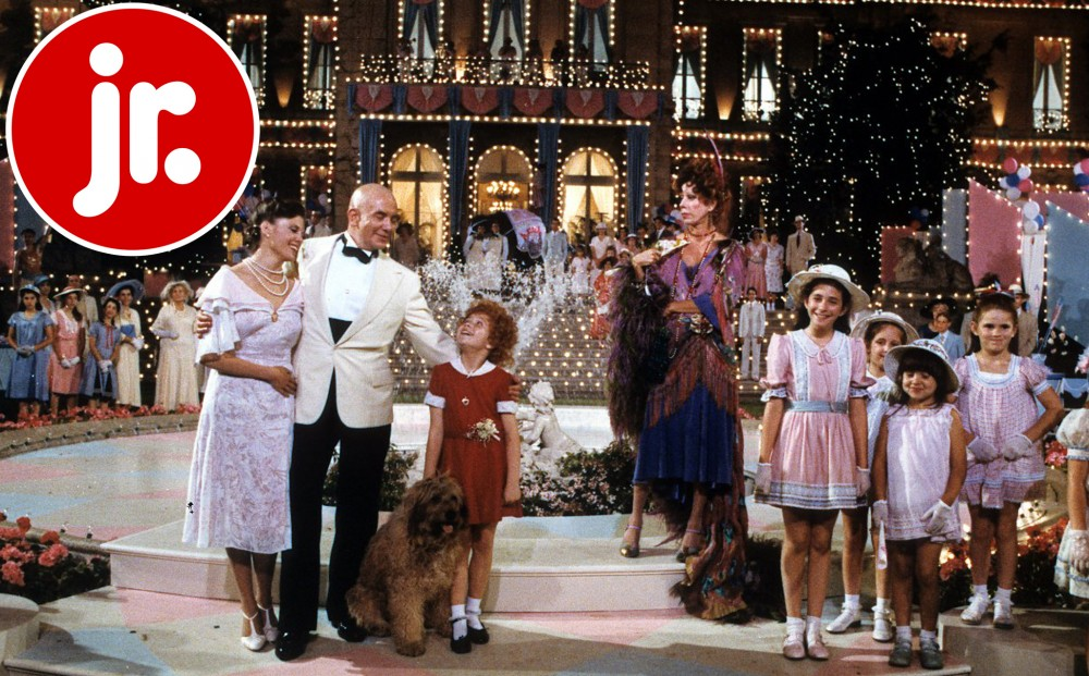 Lead character Annie stands with a man, woman, and dog, along with many other children, in front of a mansion covered in lights.