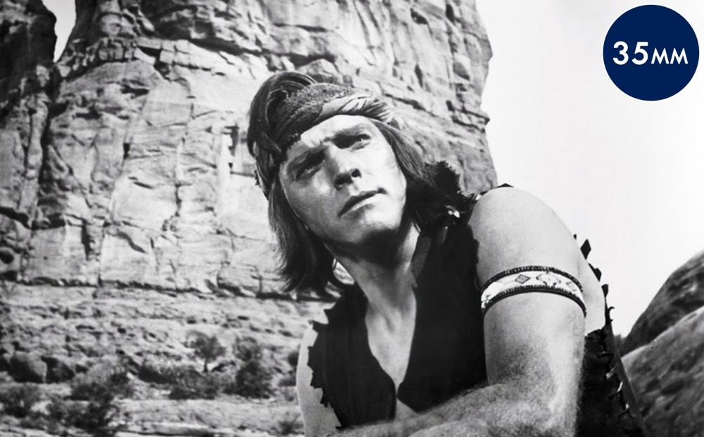 Actor Burt Lancaster kneels in front of a rocky bluff, wearing a head band and an arm band.