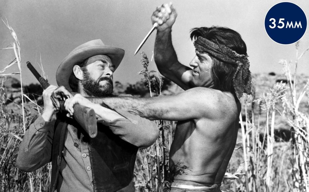 Actor Burt Lancaster wields a knife, fighting another man who holds a gun.