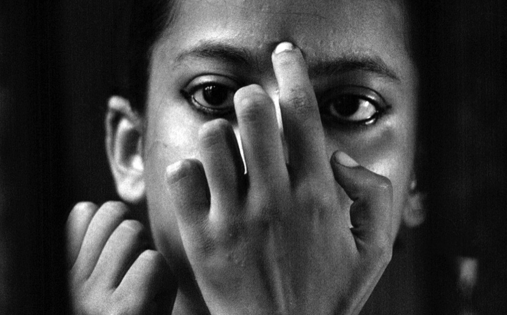 Close-up on actor Uma Das Gupta's face; her hand covering her mouth, cheeks, and nose.