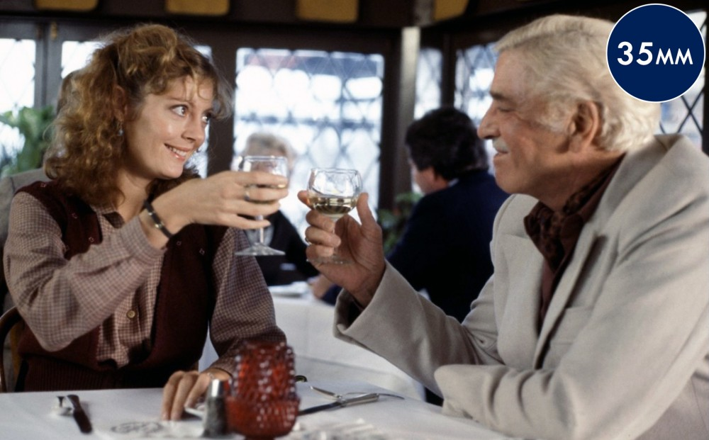 Actors Burt Lancaster and Susan Sarandon clink their glasses of white wine together, sitting at a restaurant.