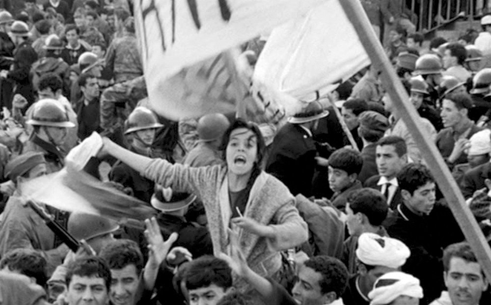 Still from THE BATTLE OF ALGIERS - A woman shouts and waves fabric in the middle of a crowd of civilians and soldiers.