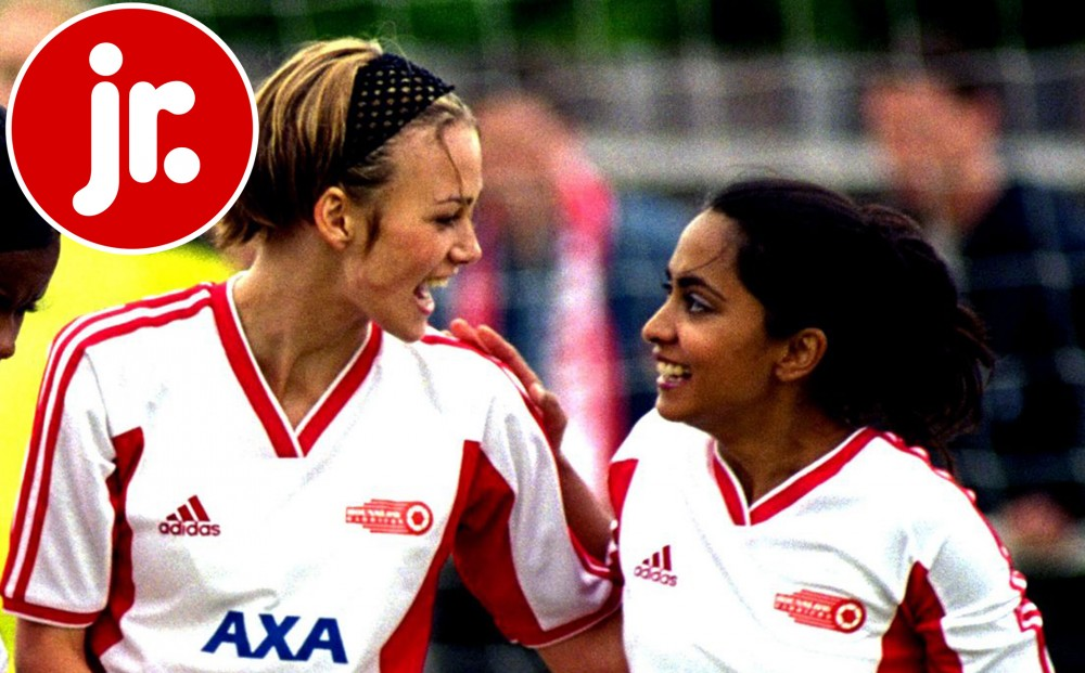 Actors Parminder Nagra and Keira Knightley look at each other triumphantly on the soccer field, in uniform.