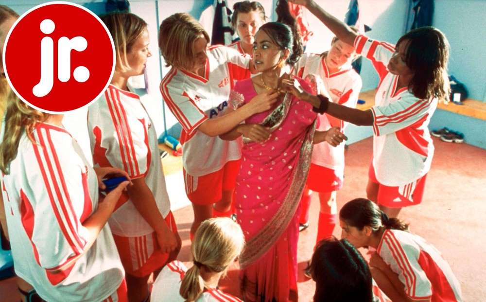 Actor Parminder Nagra wears a sari in a locker room, surrounded by a team of women in soccer uniforms, who are helping her get dressed.