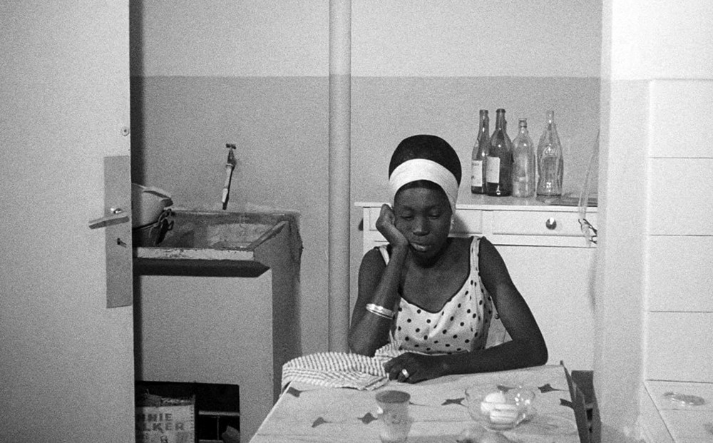 Actor Mbissine Thérèse Diop sits at a kitchen table, resting her head on her hand.
