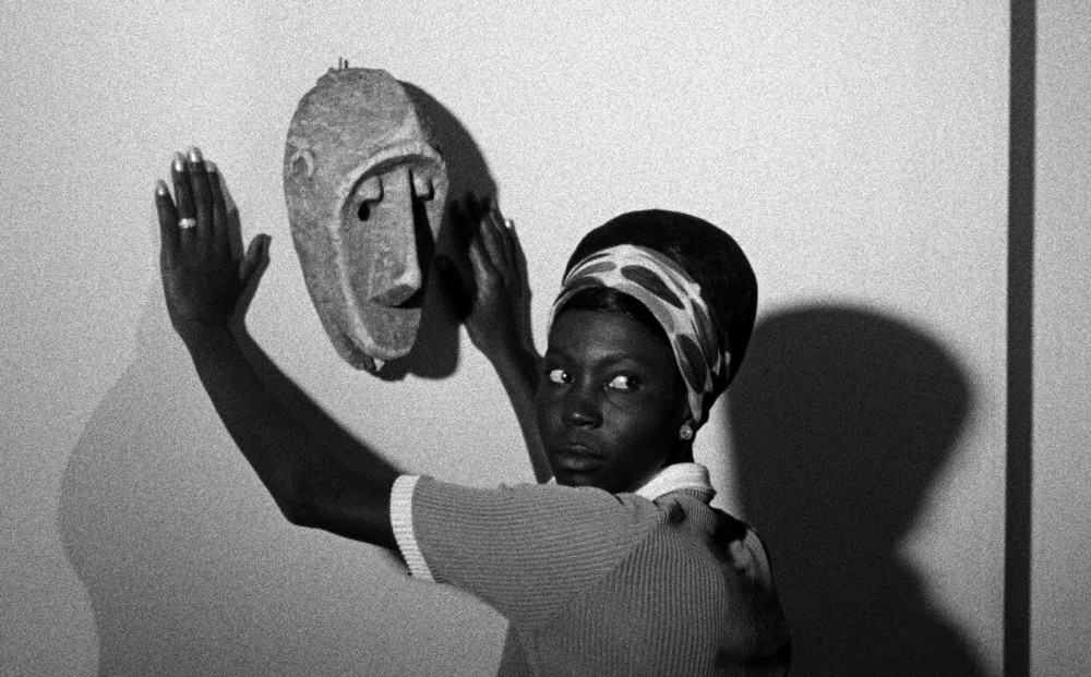 Actor Mbissine Thérèse Diop looks over her shoulder while resting her hands on a wall, where an African mask is hung on a wall.