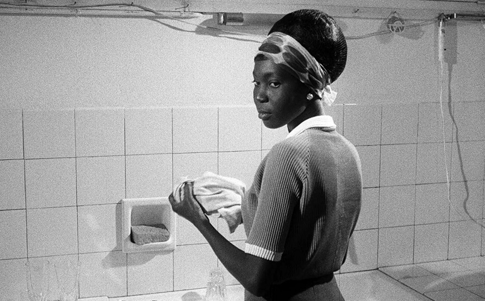 Actor Mbissine Thérèse Diop stands at a sink, holding a towel in her hands.