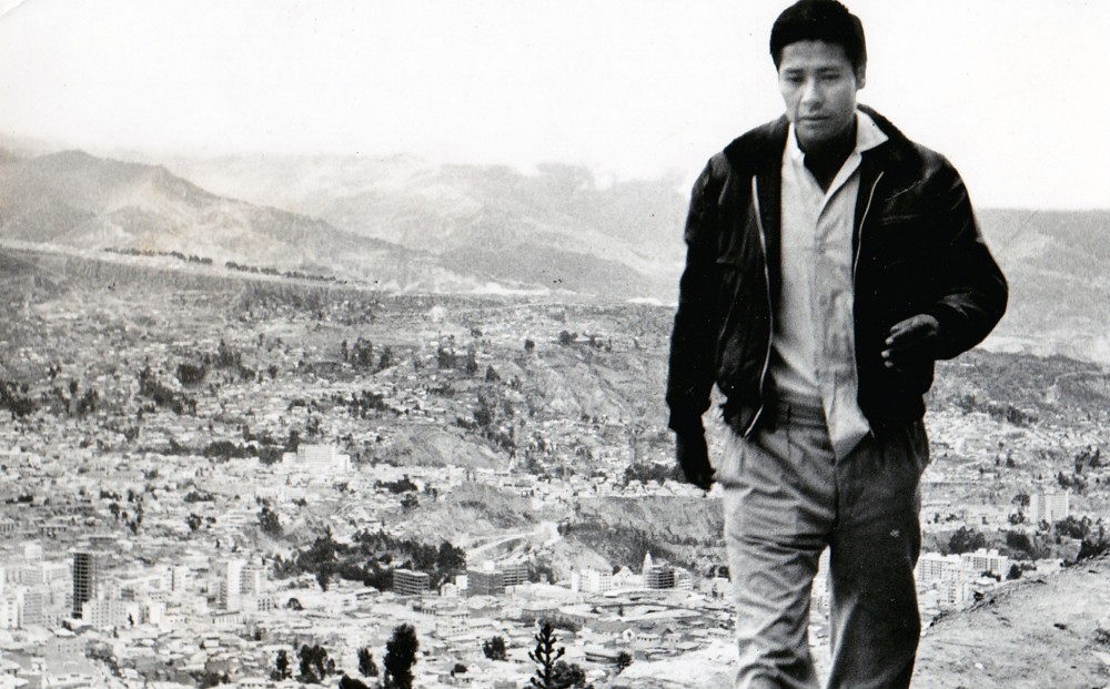 A man walks; a crowded urban area is in a valley in the background behind him.