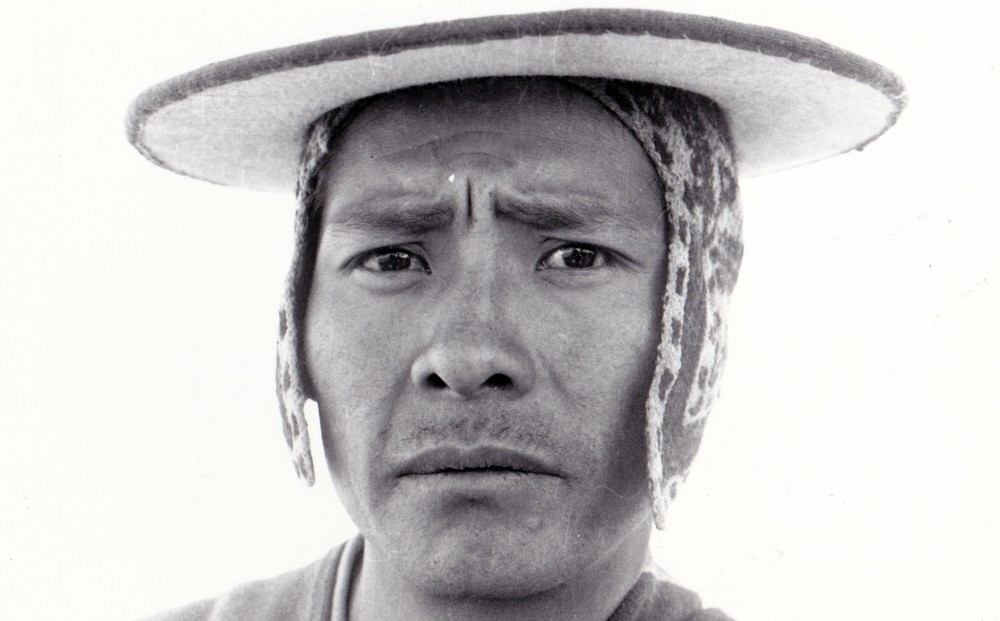 Close-up on the face of a Bolivian campesino wearing a hat.