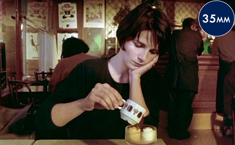 Actor Juliette Binoche sits at a table, pouring espresso over two scoops of ice cream.
