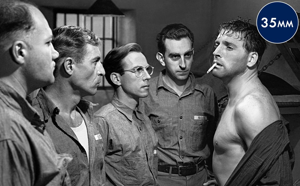 A group of men stand around Burt Lancaster, who is smoking a cigarette and has his shirt unbuttoned.