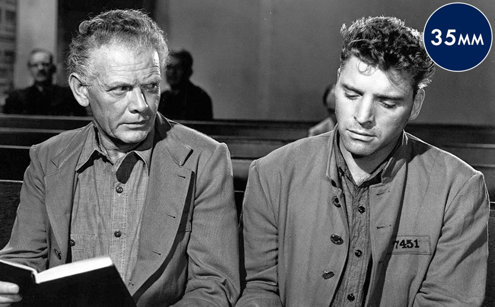 Actor Burt Lancaster sits next to another man in church pews.