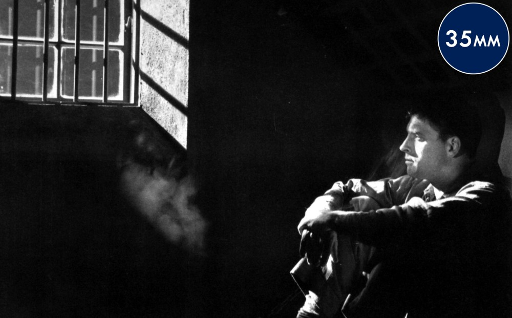 Actor Burt Lancaster sits in profile in a dark prison cell.