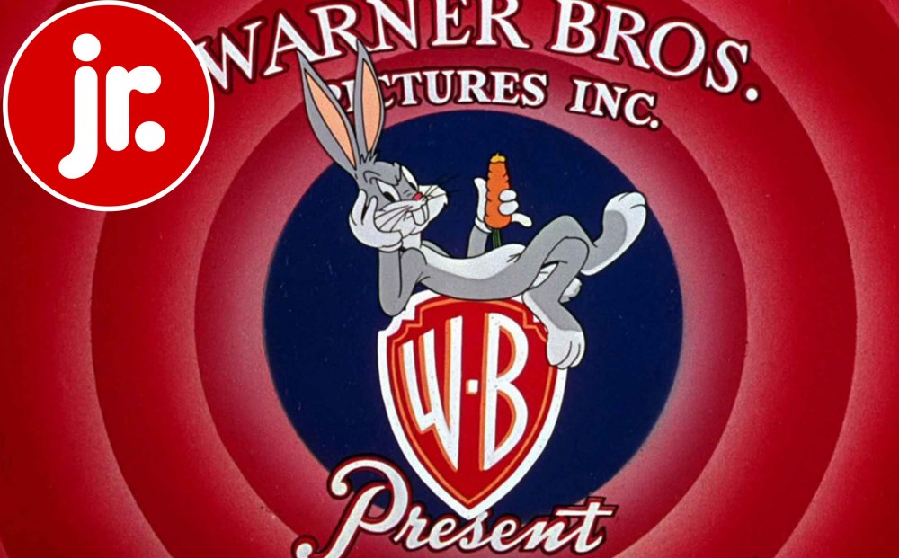 Bugs Bunny is perched on top of the Warner Brothers' logo, scowling and eating a carrot.