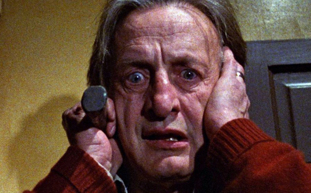 Actor George C. Scott holds his hands to his head, looking horrified.