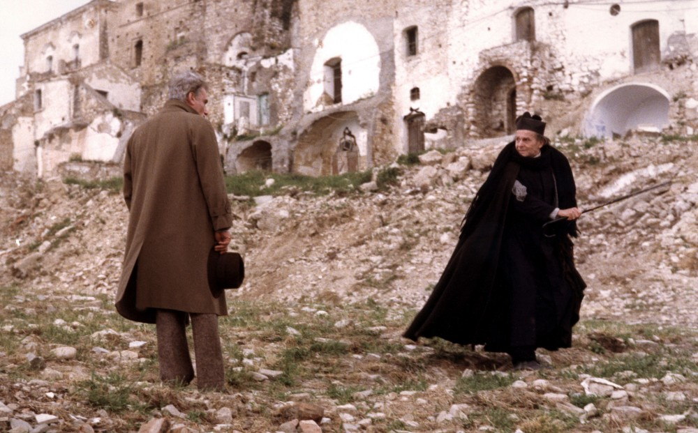 Actor Gian Maria Volontè speaks with a woman near ruins.