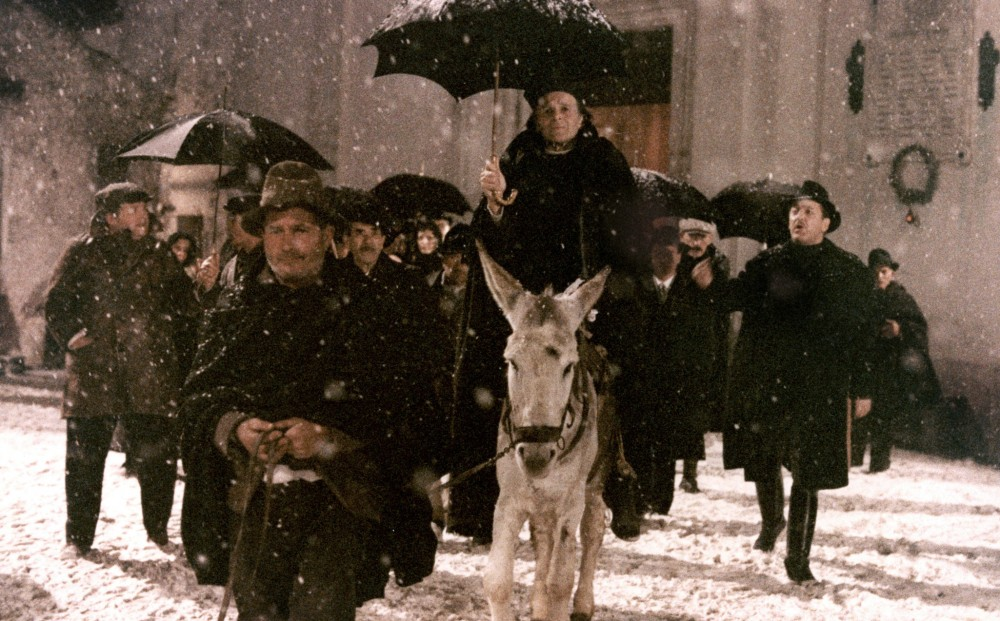 A procession of townspeople walking outside in the snow.