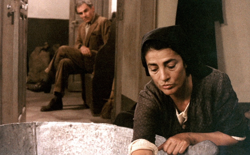 Actors Gian Maria Volontè and Irene Papas; he looks on as she scrubs a basin.