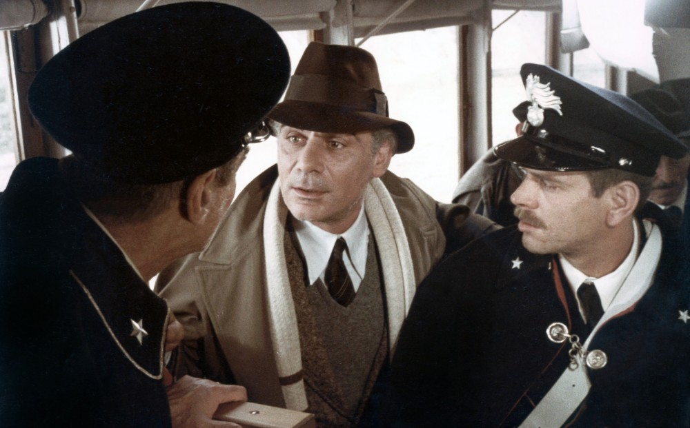 Actor Gian Maria Volontè speaks with two police officers.