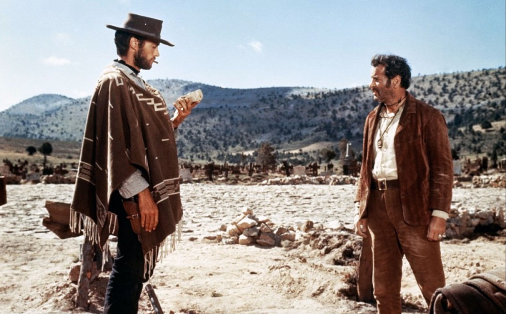 Actor Clint Eastwood stands in a barren area with another actor.