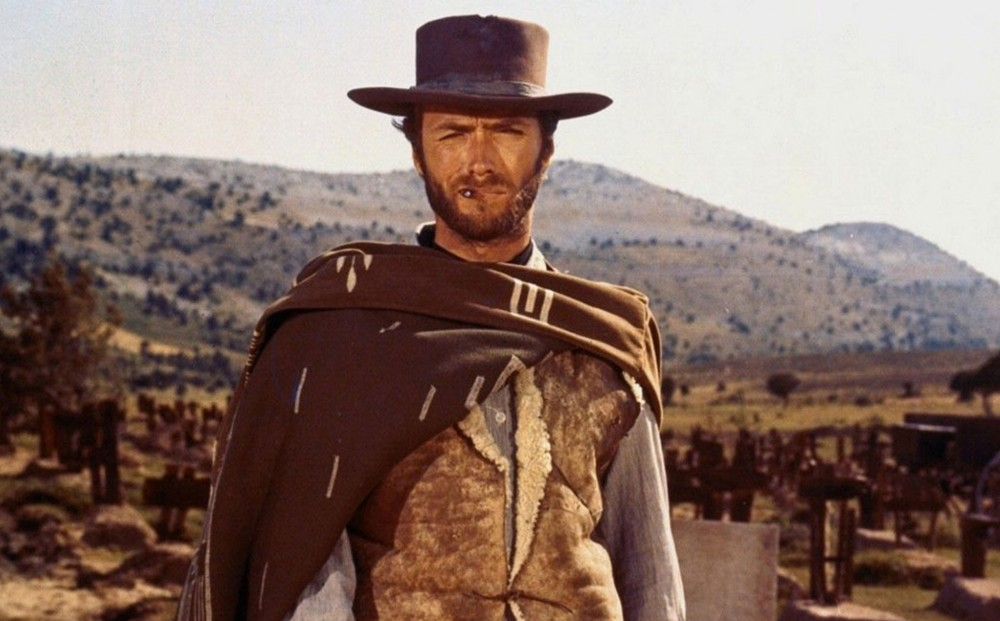 Actor Clint Eastwood stands in a landscape, smoking.