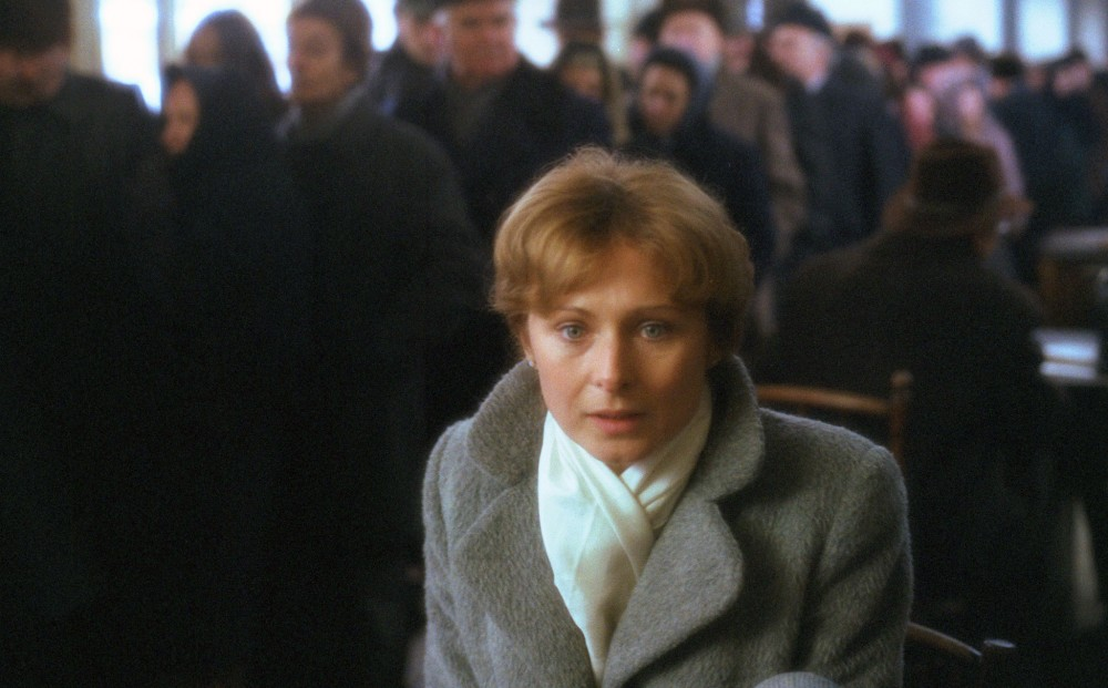 A woman in focus in the foreground, with a long line of people in the background.
